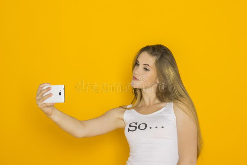 Young attractive woman make selfie on her smartphone. Fashion girl with mobile phone reads message. Studio shot orange background royalty free stock photography