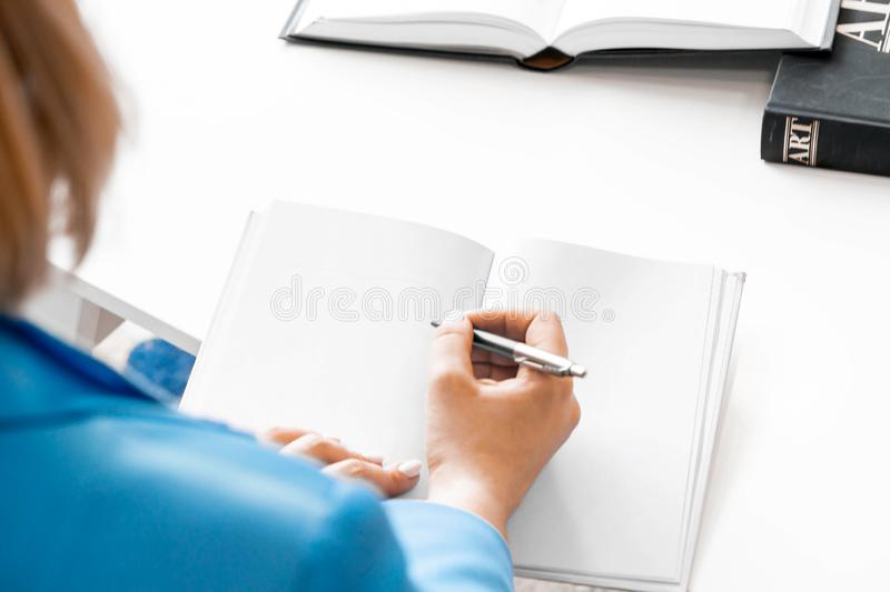 Young attractive woman makes some notes in notepad at library stock images