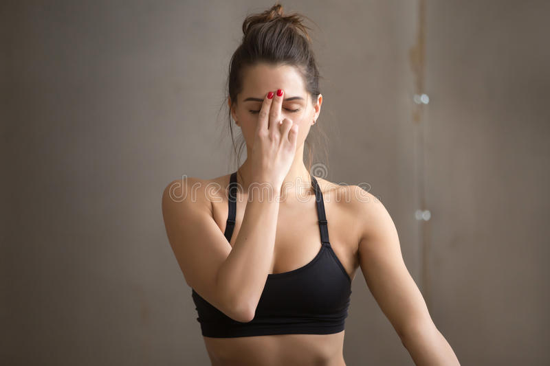 Young attractive woman making Alternate Nostril Breathing, grey. Portrait of young attractive yogi woman practicing yoga, making Alternate Nostril Breathing royalty free stock images