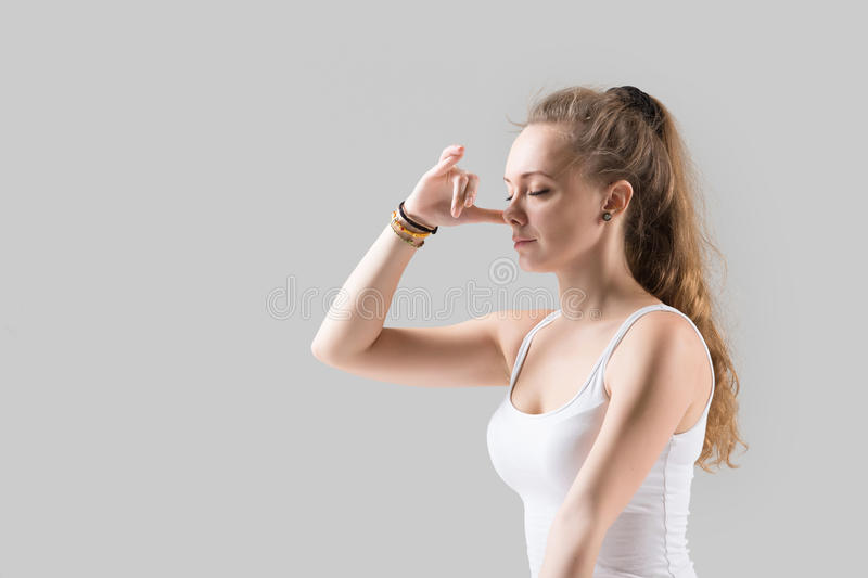 Young attractive woman making Alternate Nostril Breathing, grey. Portrait of young attractive yogi woman practicing yoga, using Alternate Nostril Breathing, nadi royalty free stock photos