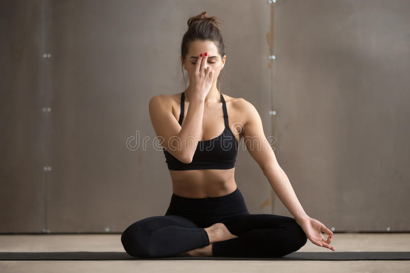 Young attractive woman making Alternate Nostril Breathing, grey. Young attractive sporty yogi woman practicing yoga, sitting in Sukhasana pose, Alternate Nostril royalty free stock photo