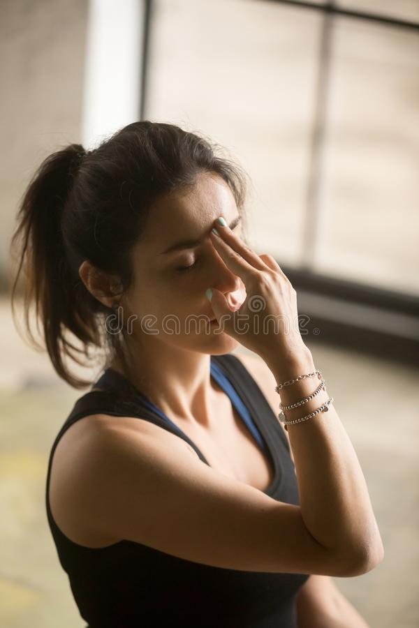 Young attractive woman making Alternate Nostril Breathing, studi. Young attractive woman practicing yoga at home, making Alternate Nostril Breathing exercise royalty free stock images