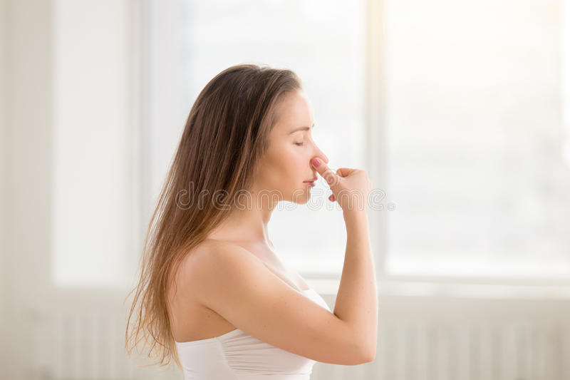 Young attractive woman making Alternate Nostril Breathing, white. Side view portrait of young attractive yogi woman practicing yoga, making Alternate Nostril stock images