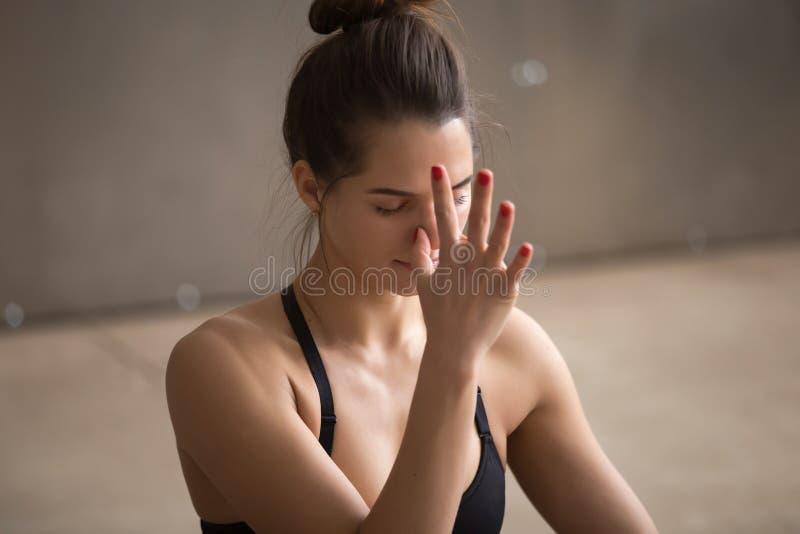 Young attractive woman making nadi shodhana pranayama, grey stud. Young attractive yogi woman practicing yoga, using Alternate Nostril Breathing, making nadi royalty free stock photos
