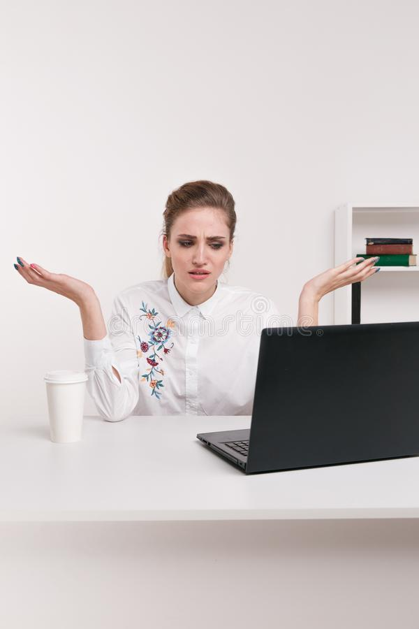 Young attractive woman at modern office desk, working on laptop, massaging temples to forget about constant headaches stock photos