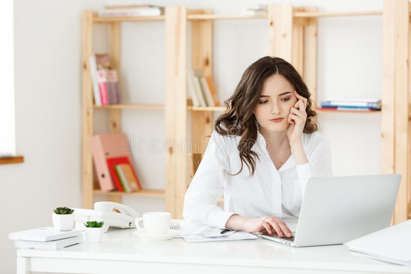 Young attractive woman at a modern office desk, working with laptop and thinking about something. Young attractive woman at a modern office desk, working with stock photo