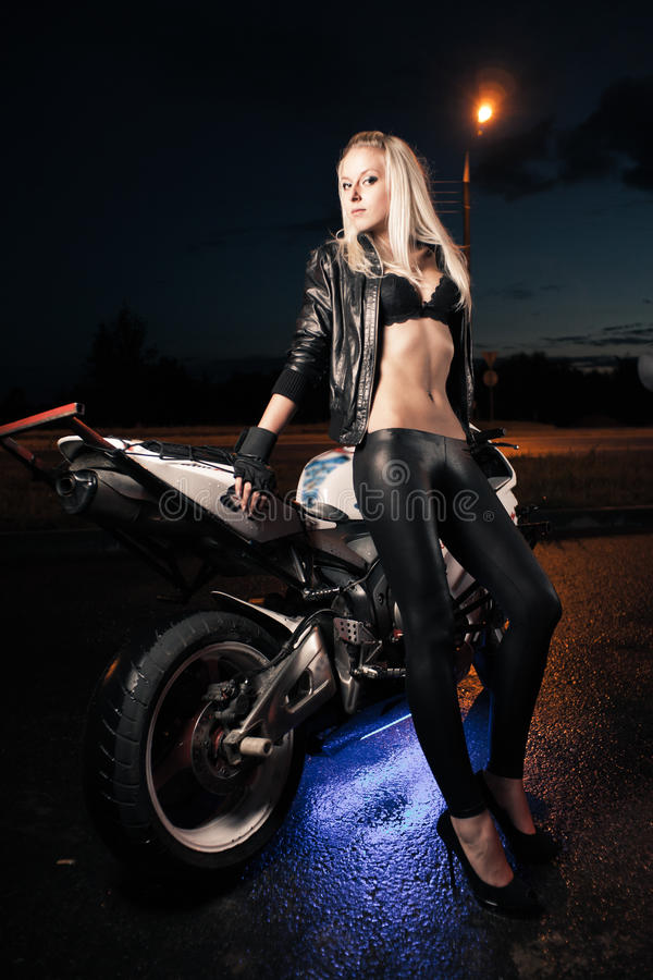Young attractive woman and motorcycle royalty free stock image
