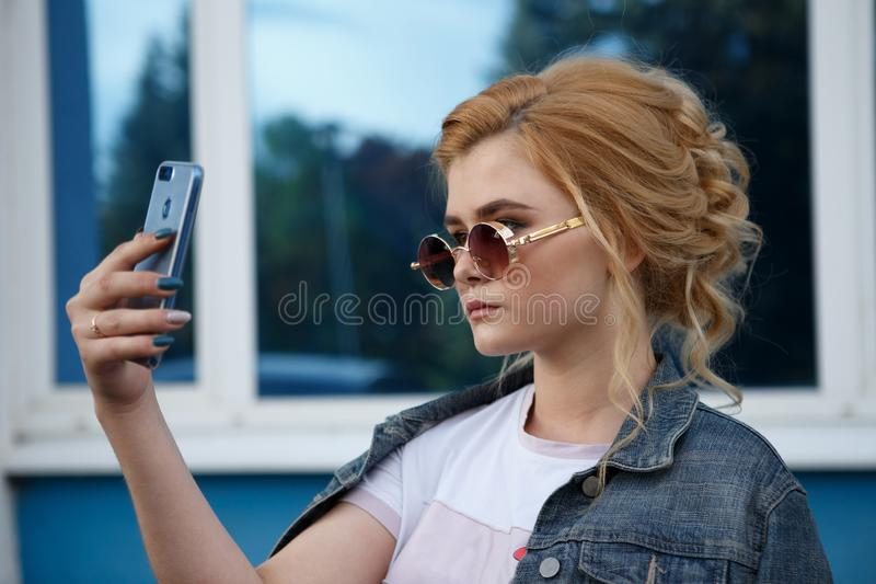 Young attractive woman in the Park, she texting with her smartphone and looking stock photos