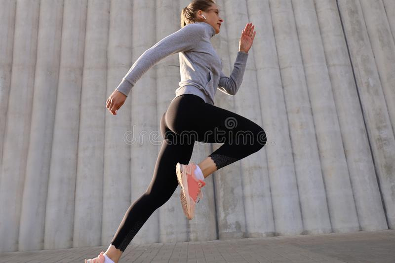 Young attractive woman with perfect slim body running outdoors. Fitness and running concept royalty free stock images