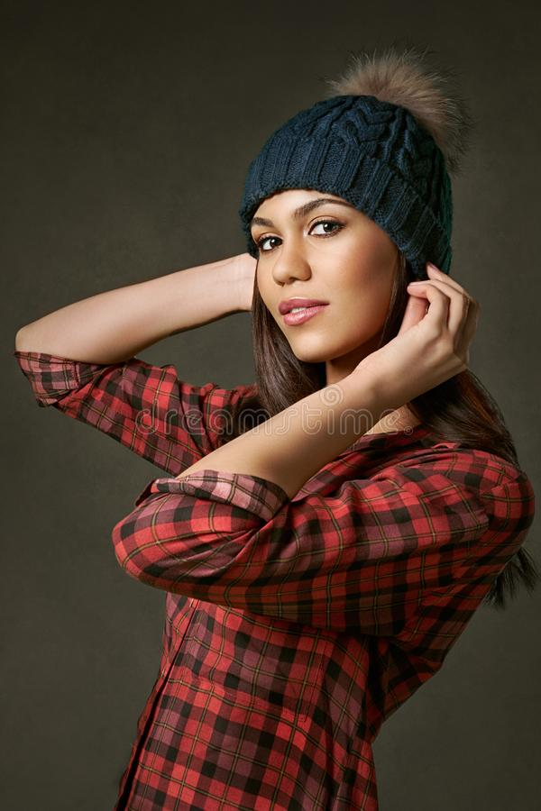 Young, attractive, woman in a plaid shirt adjusting a winter hat.. royalty free stock image