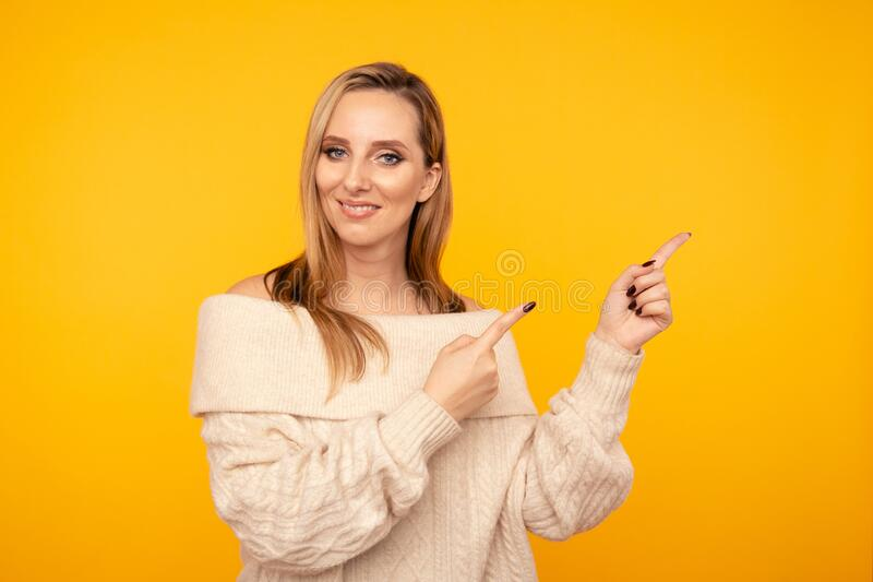 Young attractive woman pointing by fingers isolated. royalty free stock image