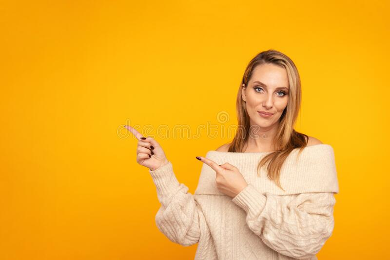Young attractive woman pointing by fingers isolated. stock photography