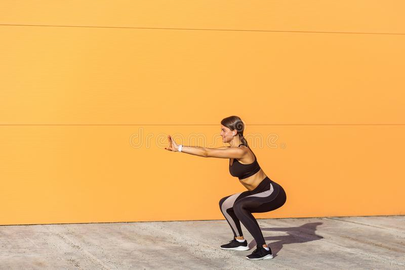 Young attractive woman practicing fitness, doing bodyweight squat exercise, yoga chair pose, working out, wearing black sportswear. Black pants and top, outdoor stock photography