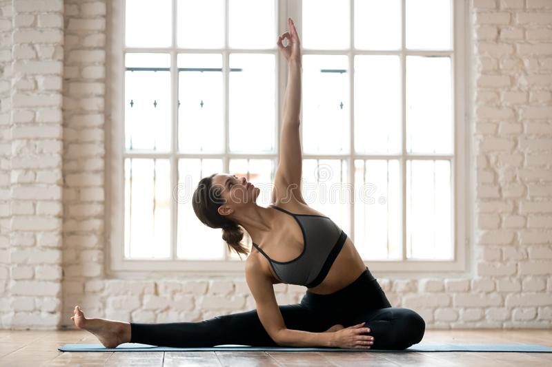 Young attractive woman practicing yoga, Parivrtta Janu Sirsasana. Young attractive woman practicing yoga, doing Revolved Head to Knee Forward exercise, Parivrtta royalty free stock images