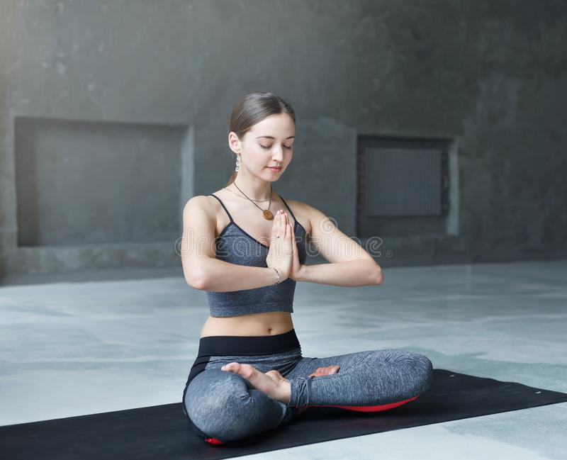Young attractive woman practicing yoga sitting in padmasana stock images