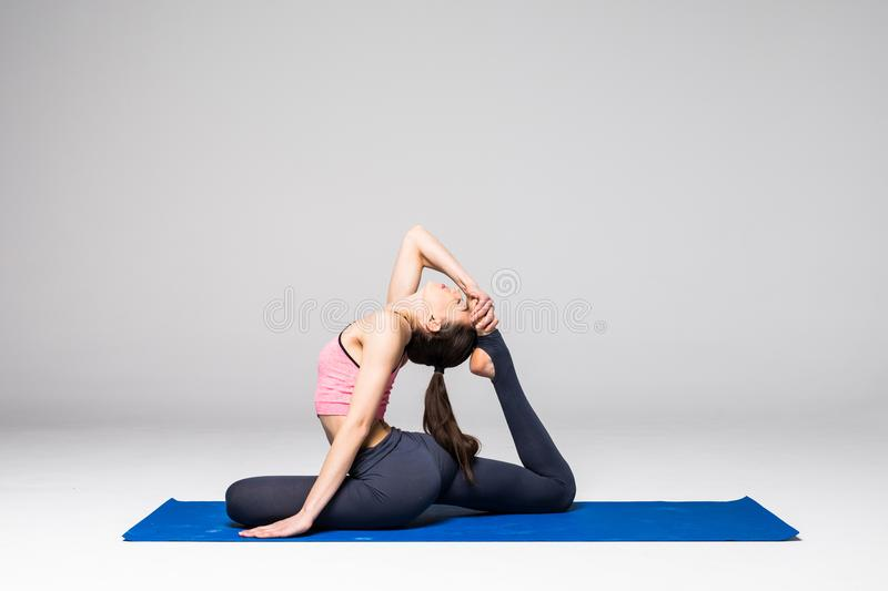 Young attractive woman practicing yoga, standing in different yoga exercise, wearing sportswear isolated on grey background. Serie. Young attractive woman royalty free stock photography