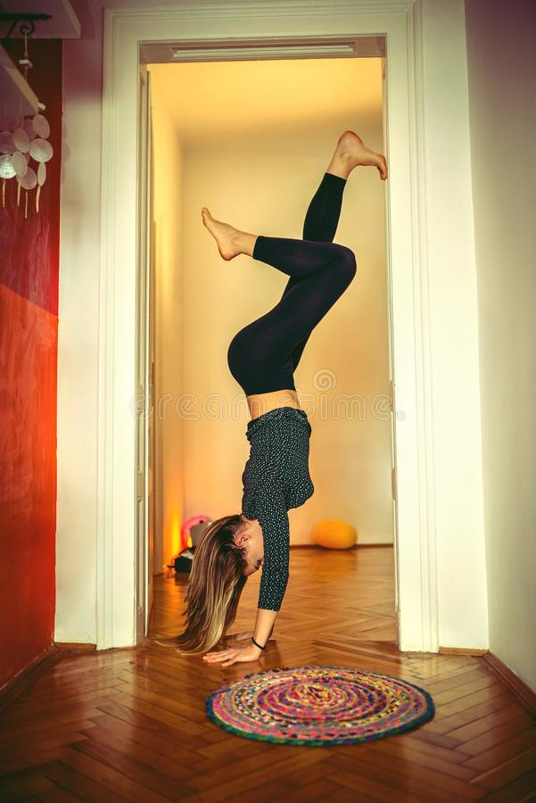 Young woman practicing yoga handstand royalty free stock images