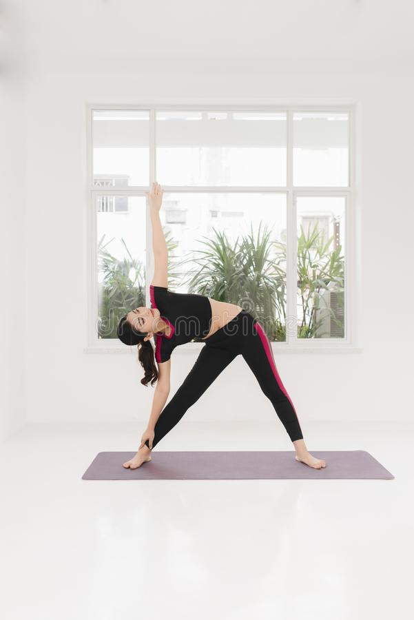 Young attractive woman practicing yoga, standing in Warrior two exercise, wearing sportswear, indoor full length near window.  stock images
