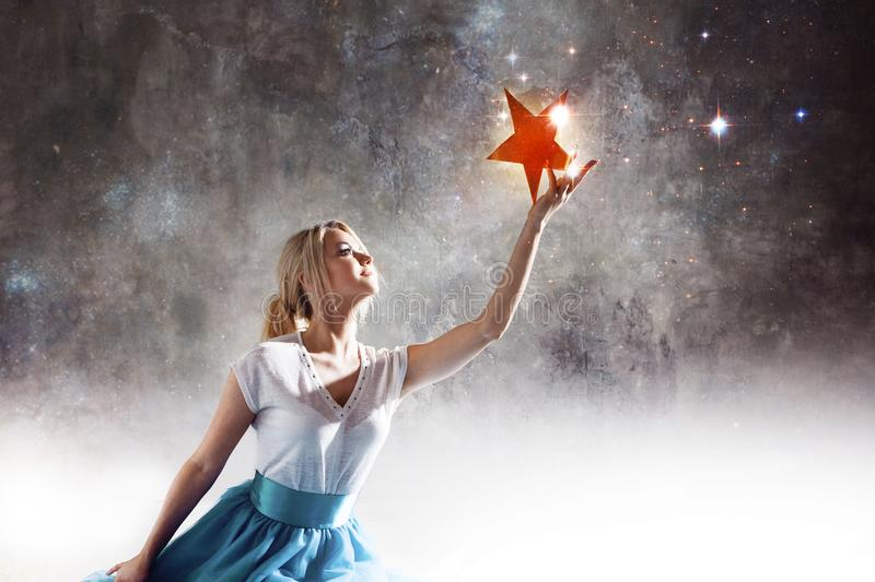 Young attractive woman reaching for the star. Take a star from the sky, dreams and plans, concept royalty free stock image