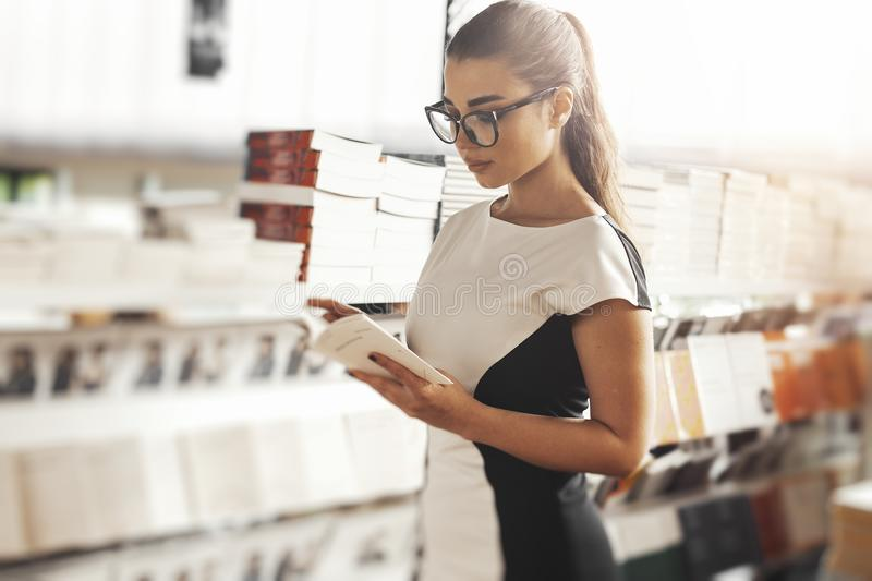 Young attractive woman reading book in a book store next to book shelf. stock image