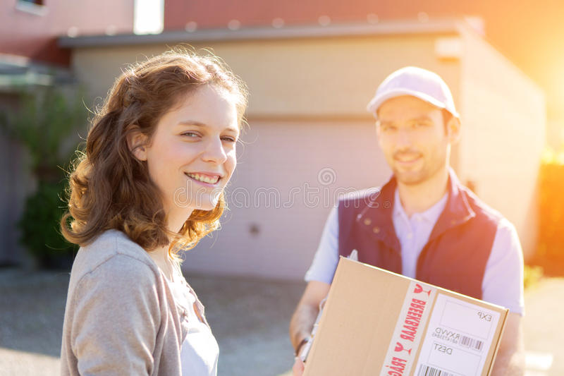 Young attractive woman receiving parcel at home. View of a Young attractive women receiving parcel at home stock photos