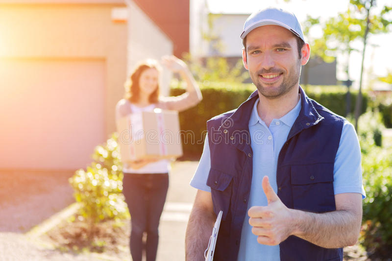 Young attractive woman receiving parcel at home. View of a Young attractive women receiving parcel at home royalty free stock image