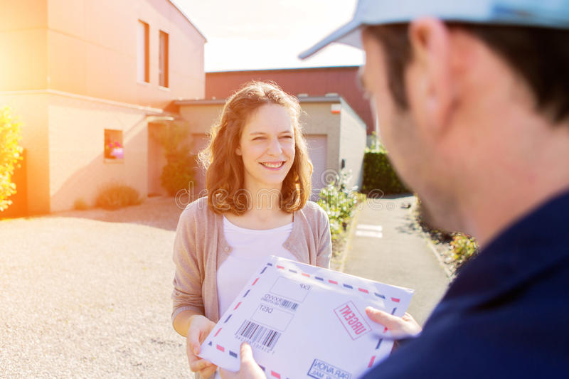 Young attractive woman receiving parcel at home. View of a Young attractive women receiving parcel at home royalty free stock photography