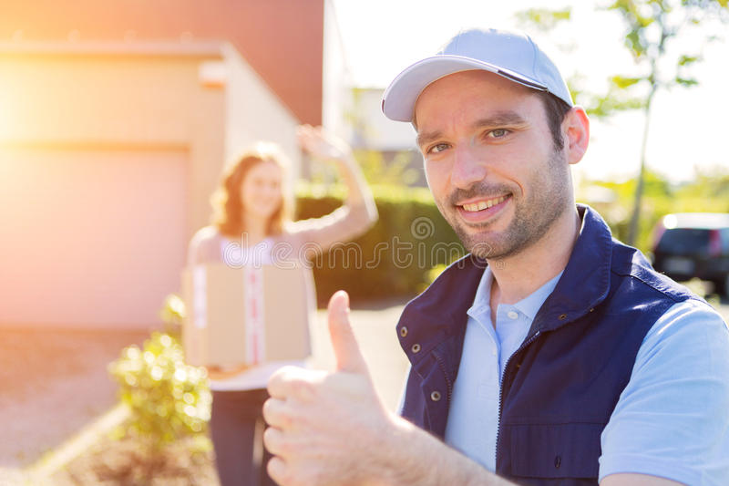 Young attractive woman receiving parcel at home. View of a Young attractive women receiving parcel at home royalty free stock photos
