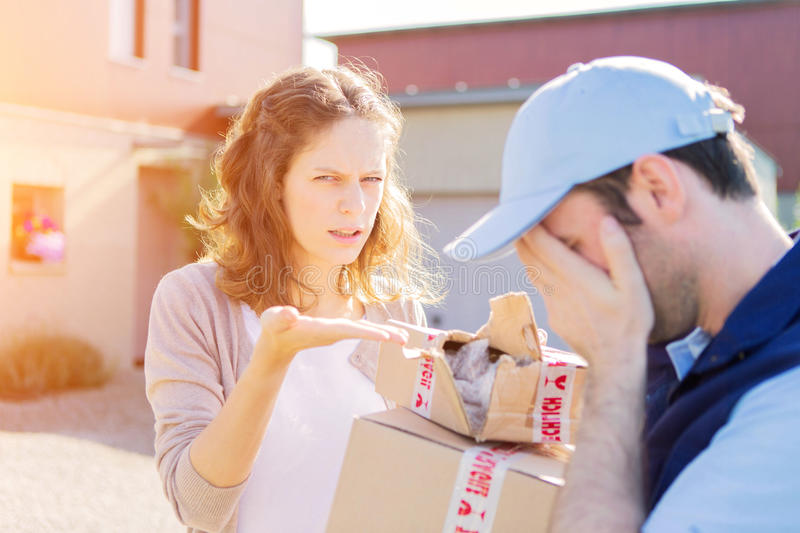Young attractive woman receiving parcel at home. View of a Young attractive women receiving parcel at home stock photo