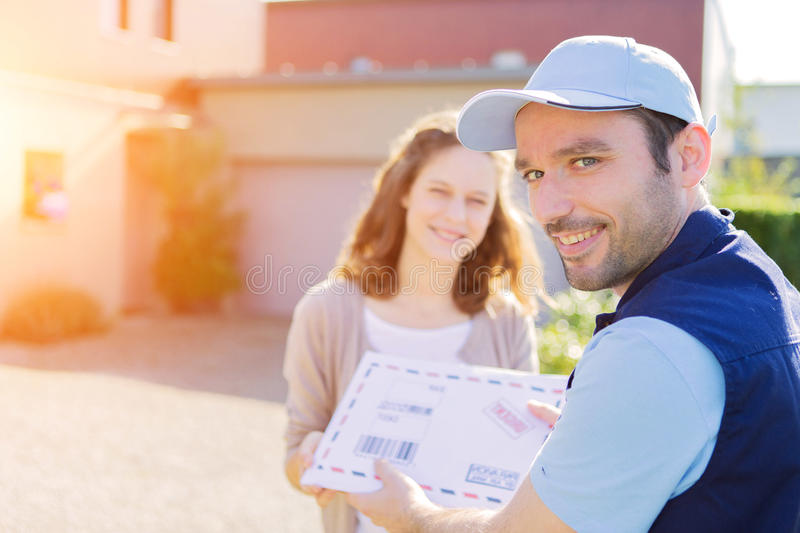 Young attractive woman receiving parcel at home. View of a Young attractive women receiving parcel at home stock image