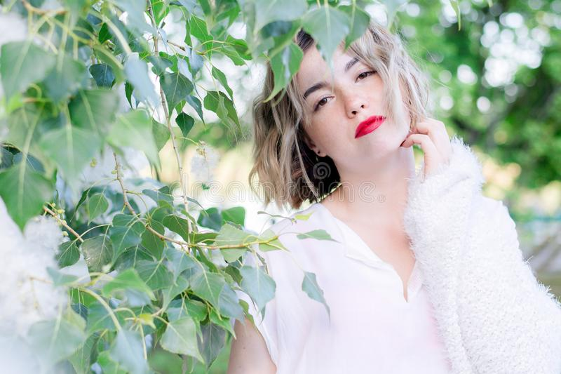 Young attractive woman with red lips in white casual clothes walking posing in the park stock photography