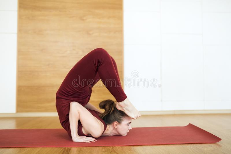 Young attractive woman in a red suit practicing yoga, standing in Scorpion exercise, vrischikasana pose, working out, wearing spor stock images
