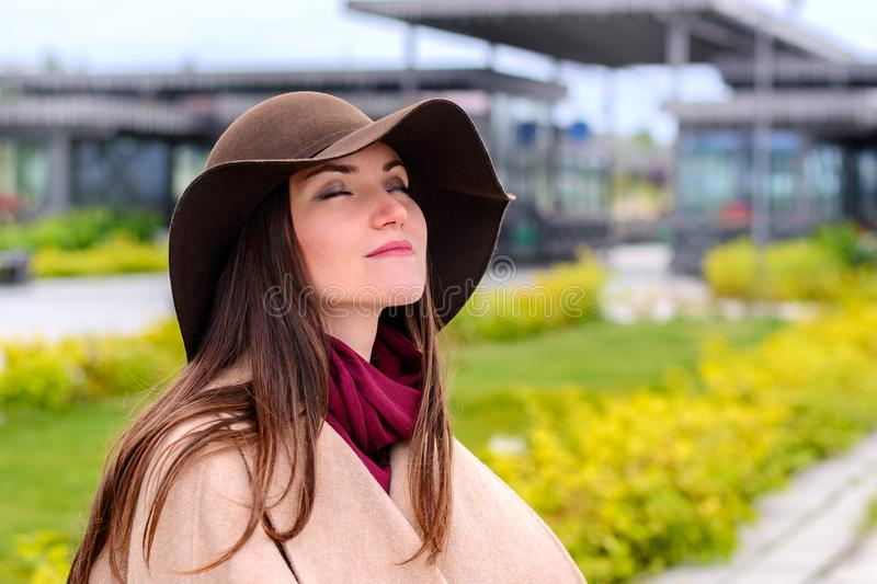 Young attractive woman in sandy coat and brown hat on, a breath of fresh air in a city Park on the waterfront stock photography