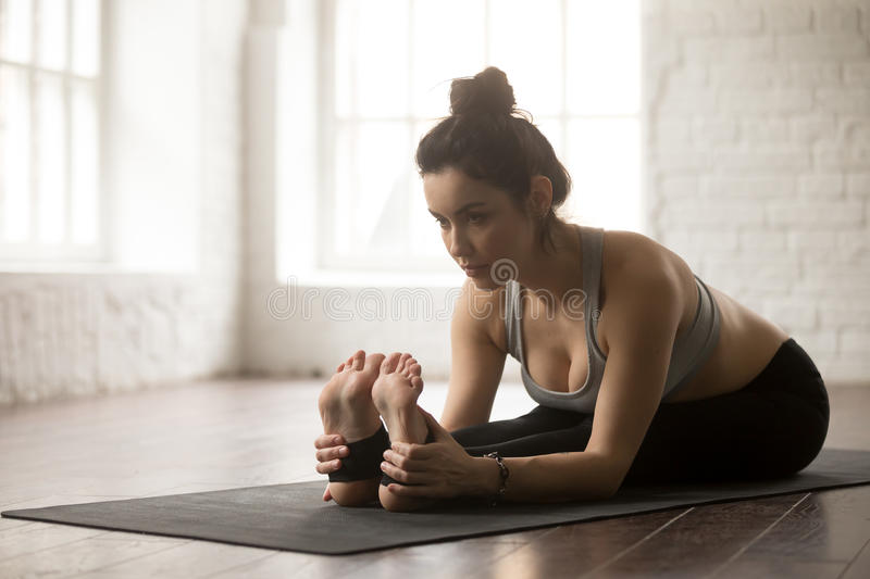 Young attractive woman in seated forward bend pose, white studio royalty free stock images