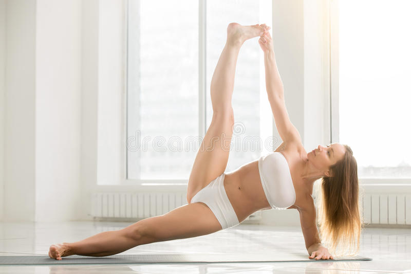 Young attractive woman in Side Plank pose, white color backgroun royalty free stock image