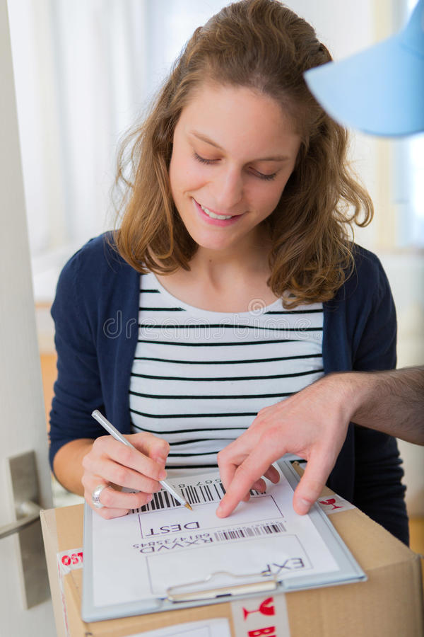 Young attractive woman signing delivery note royalty free stock image