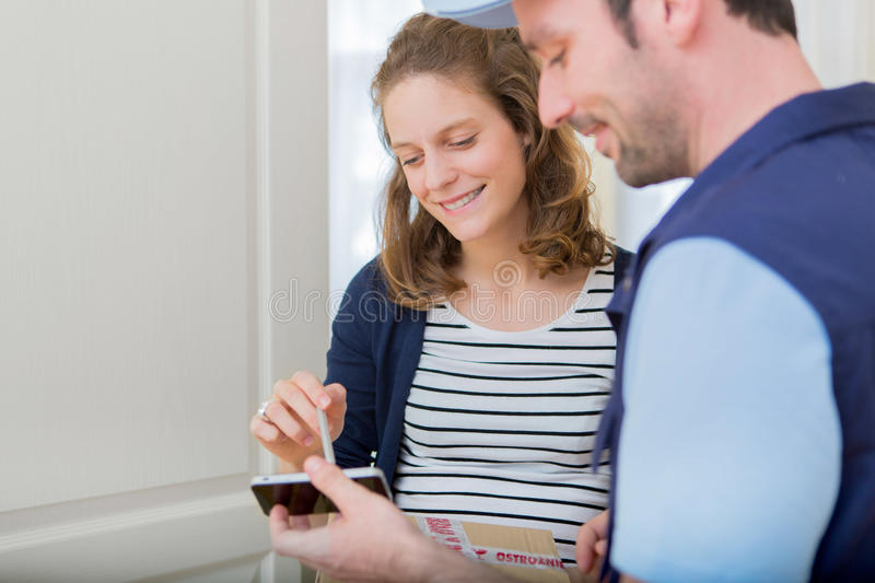 Young attractive woman signing on delivery paper stock photography