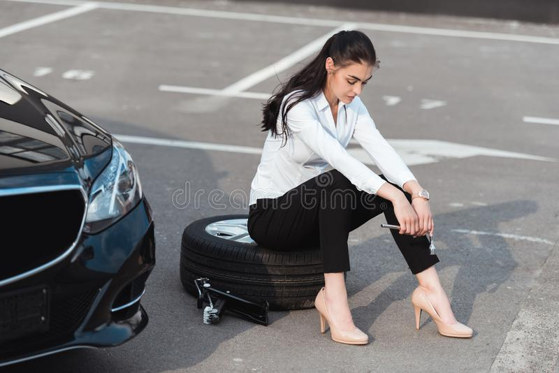 Young attractive woman sitting on car tire with lug wrench in her hand stock images