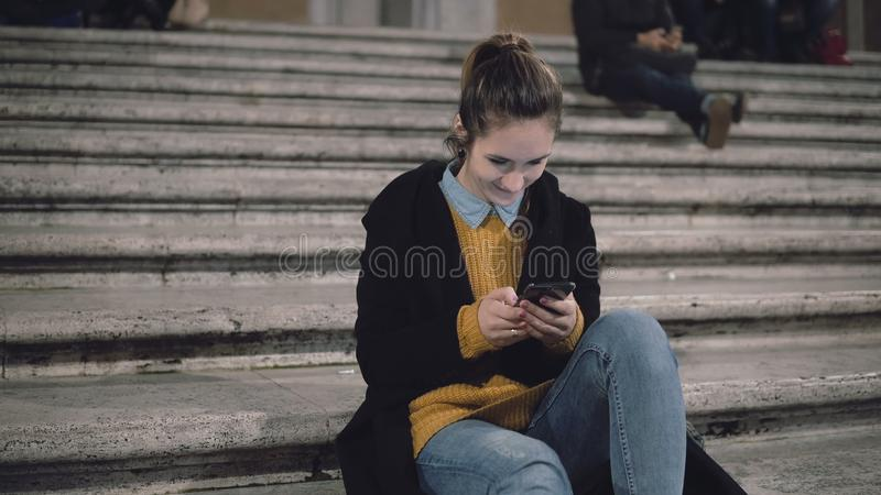 Young attractive woman sitting at the ladder in the city and use smartphone. Student girl texting with friends. royalty free stock photos
