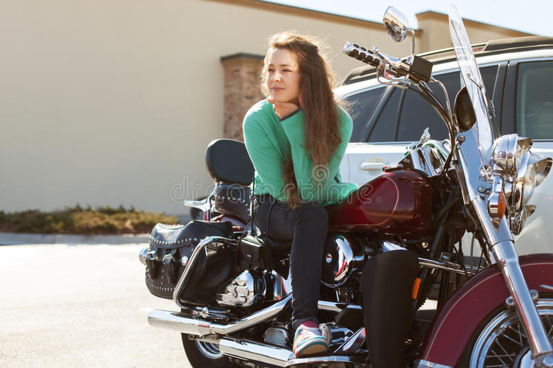 Young attractive woman is sitting on red motorcycle and looking aside on the road seriously royalty free stock image