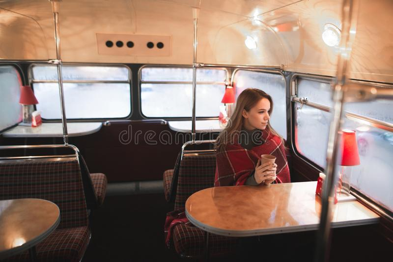 Young attractive woman sitting at the table in the bus cafe is covered with a blanket royalty free stock photos