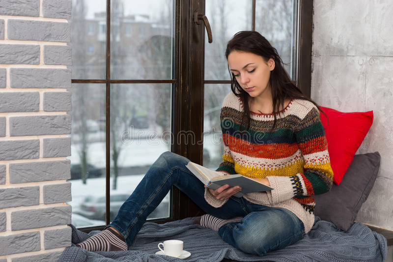 Young attractive woman sitting on the windowsill and reading a b. Young attractive woman in warm knitted sweater sitting on the windowsill with pillows and stock images
