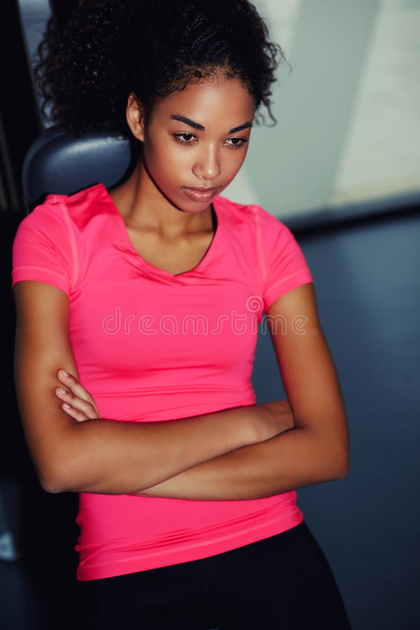 Young attractive woman with a slender figure and dark skin a rest after a hard workout. Portrait of young afro american woman wearing pink t-shirt relaxing after royalty free stock photo