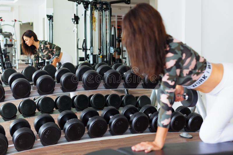 Sportive woman with slim body doing exercise with dumbbell royalty free stock photography