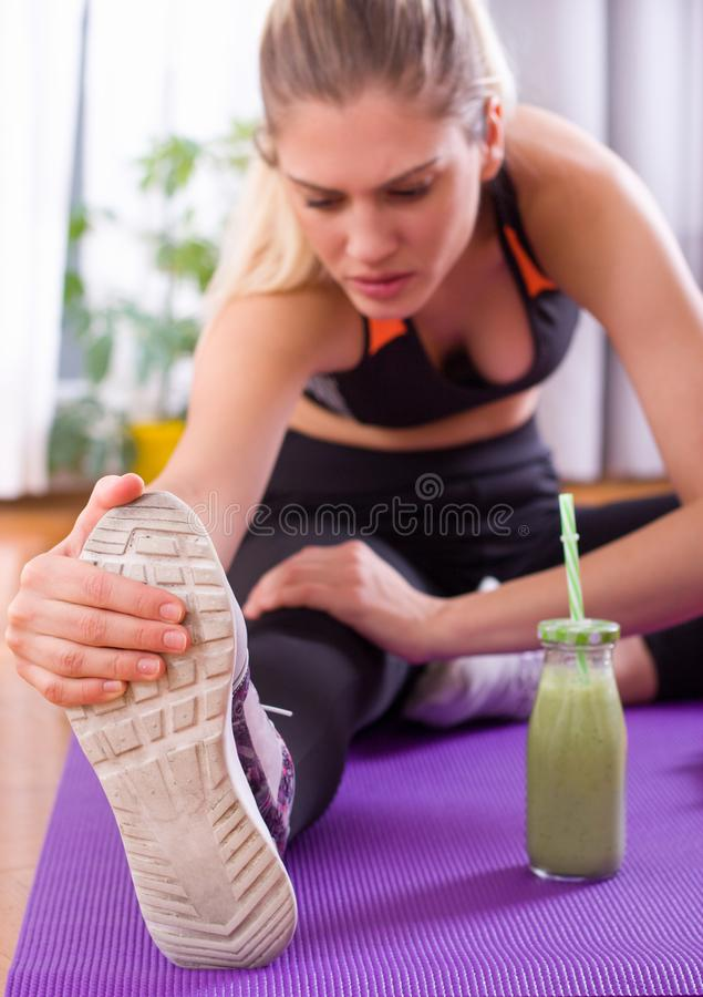 Pretty woman stretching legs on floor after workout royalty free stock photography