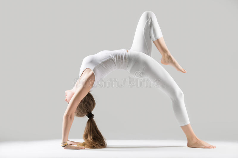 Young attractive woman standing in Bridge pose, grey studio back royalty free stock photo