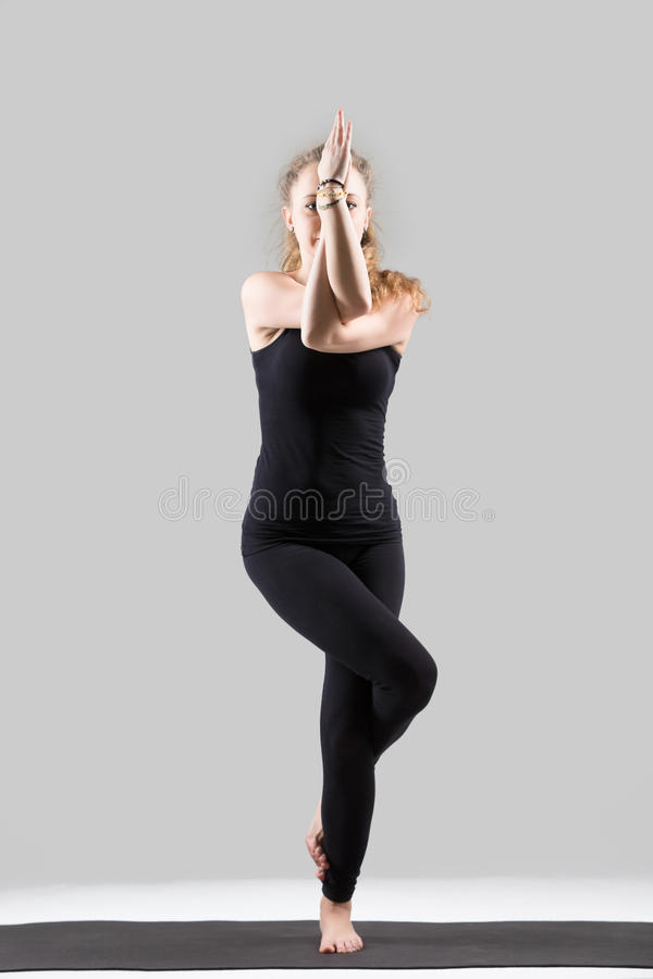 Young attractive woman standing in Garudasana pose, grey studio stock images