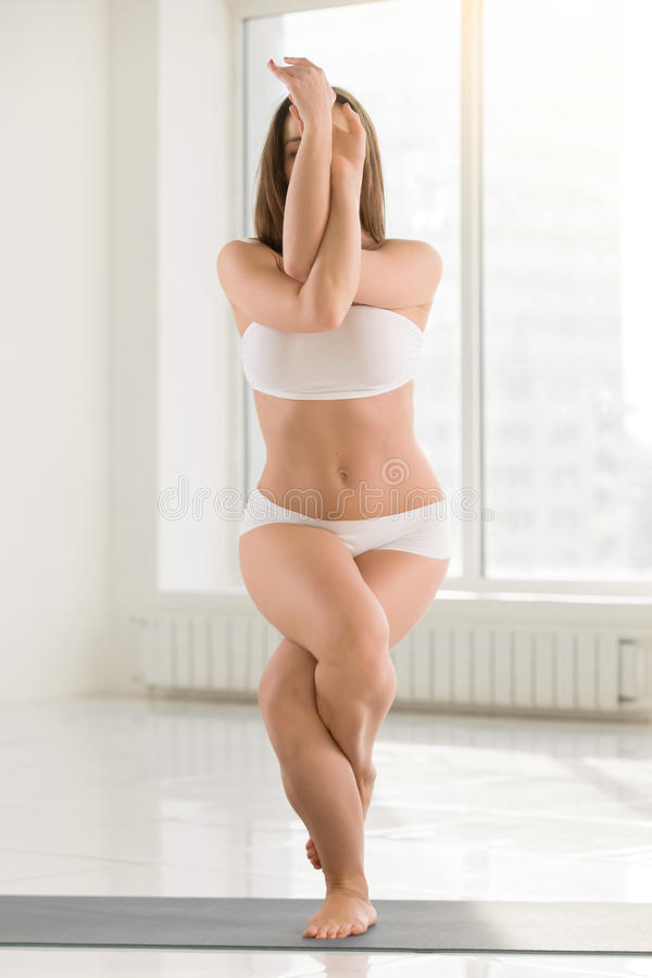 Young attractive woman standing in Garudasana pose, white color stock photography
