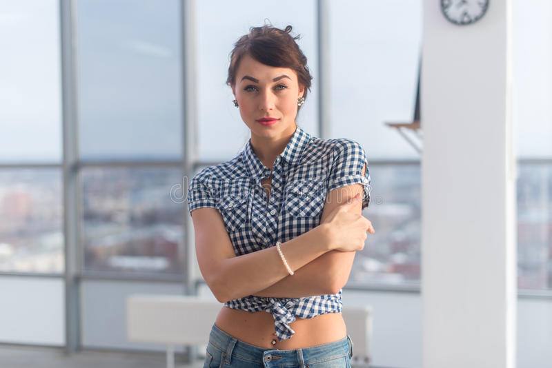 Young attractive woman standing, holding arms crossed, wearing blue denim pants, having flat naked stomach with piercing.  royalty free stock photography