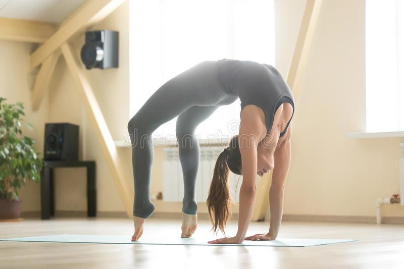 Young attractive woman standing in Urdhva Dhanurasana pose, home. Young cool attractive woman practicing yoga, standing in Urdhva Dhanurasana exercise, Bridge royalty free stock image
